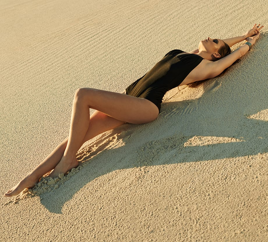 Woman laying on sand in bathing suit