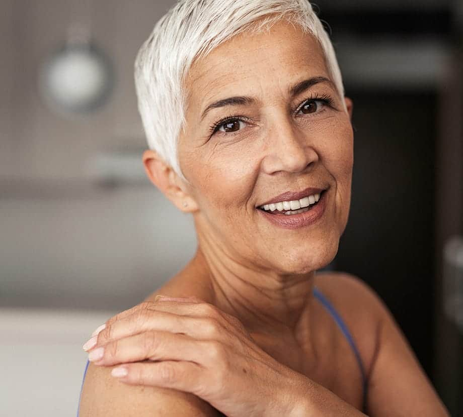 Older woman smiling with her hand on her shoulder