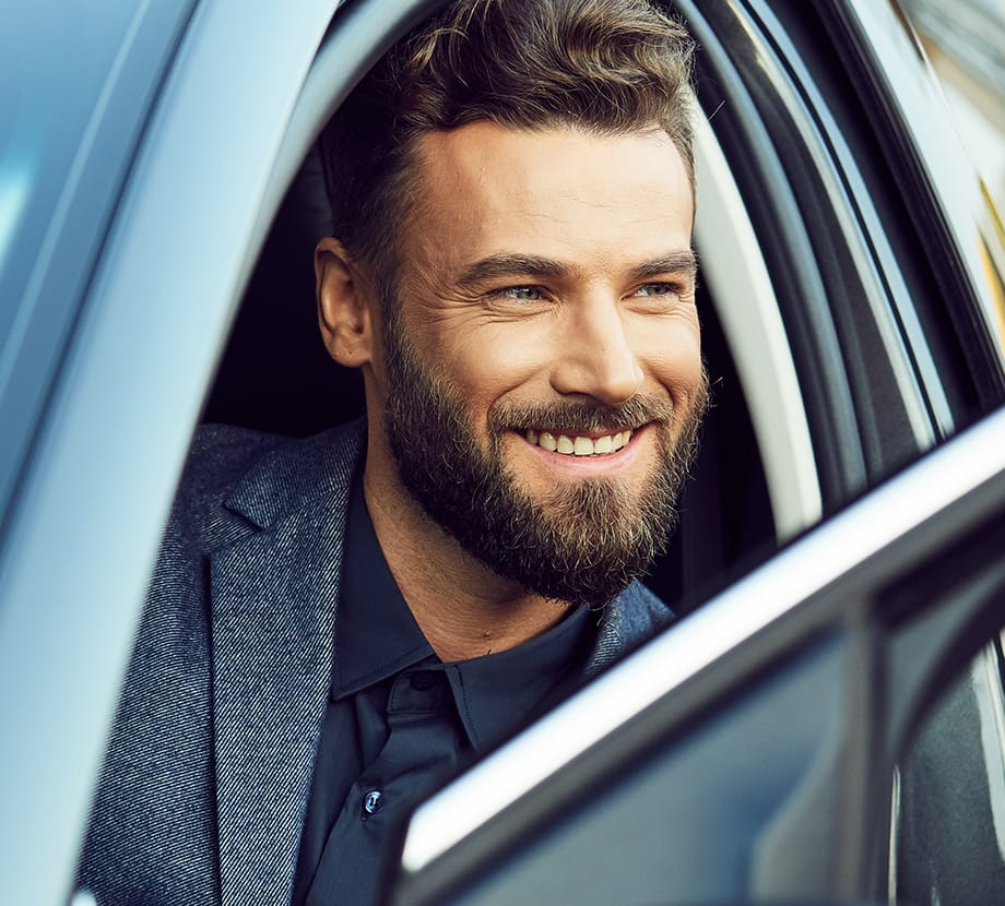 Man sitting in car while looking out window