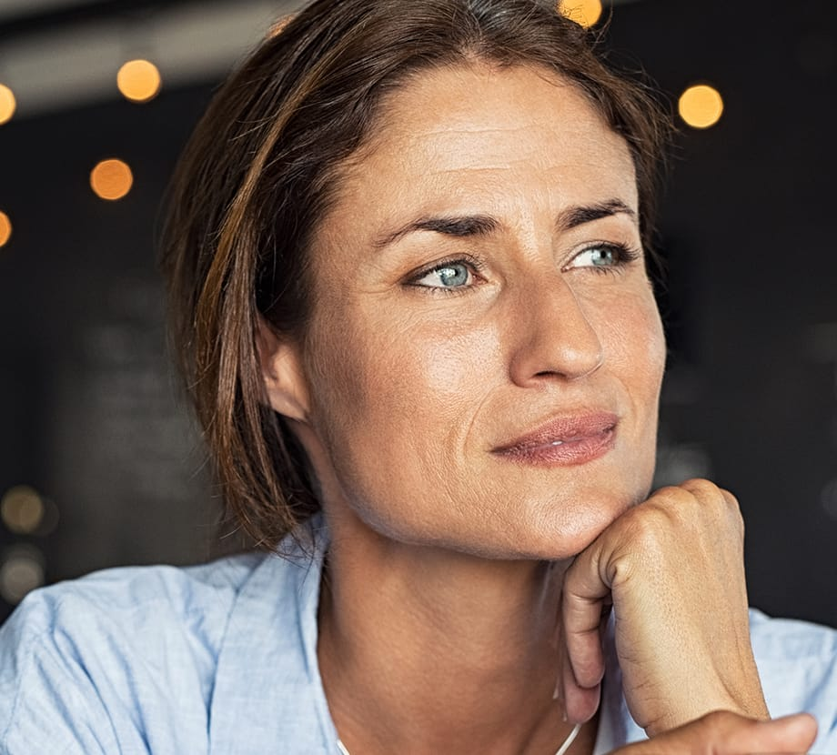 Older woman resting her chin on hand while looking to side