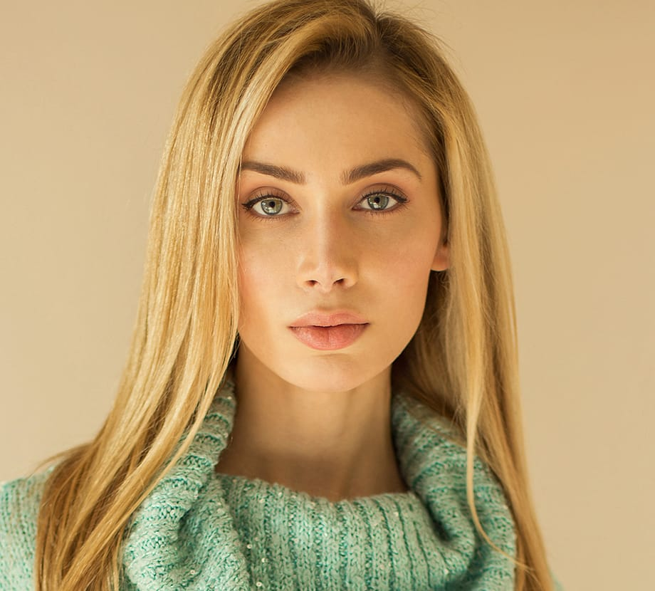 Blonde haired woman looking seriously into camera