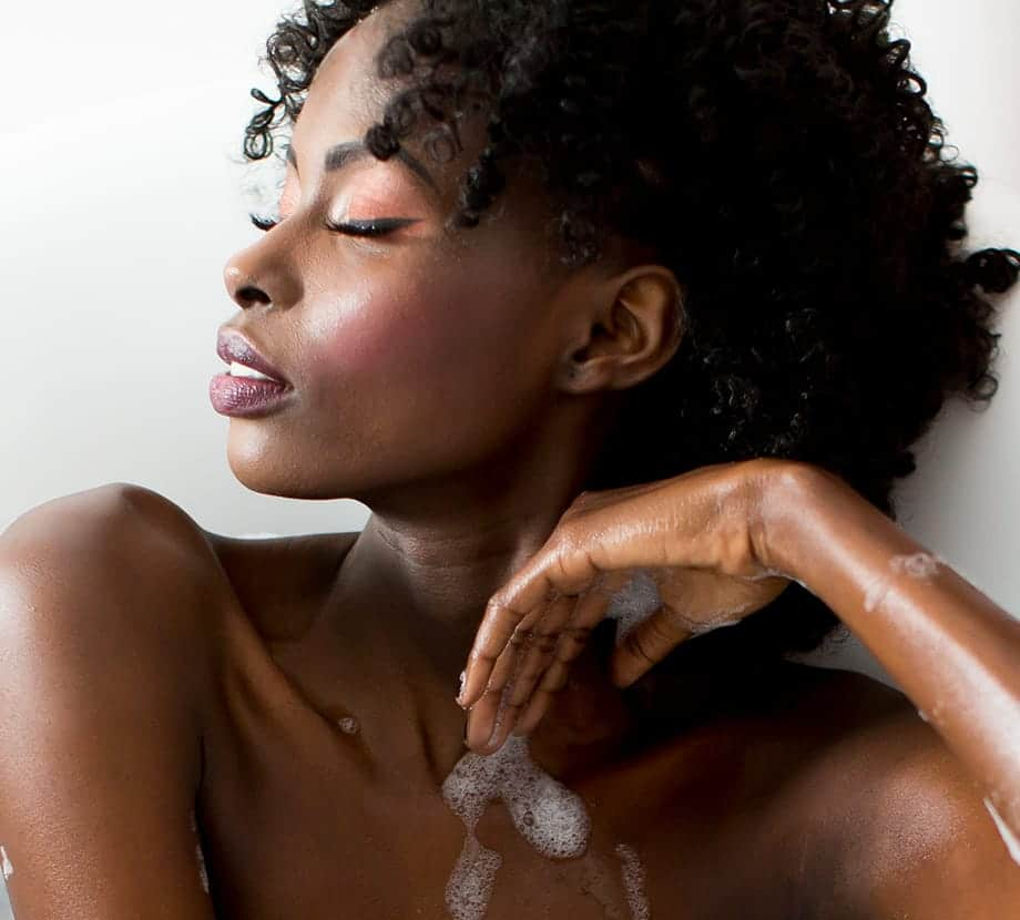 Woman sitting in a bath with bubbles on her arm