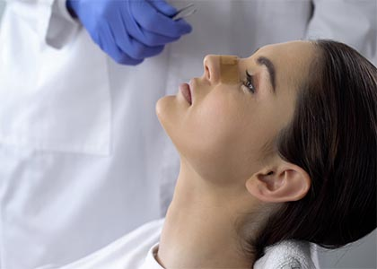 Lady with plaster on nose, doctor examining patients face after plastic surgery